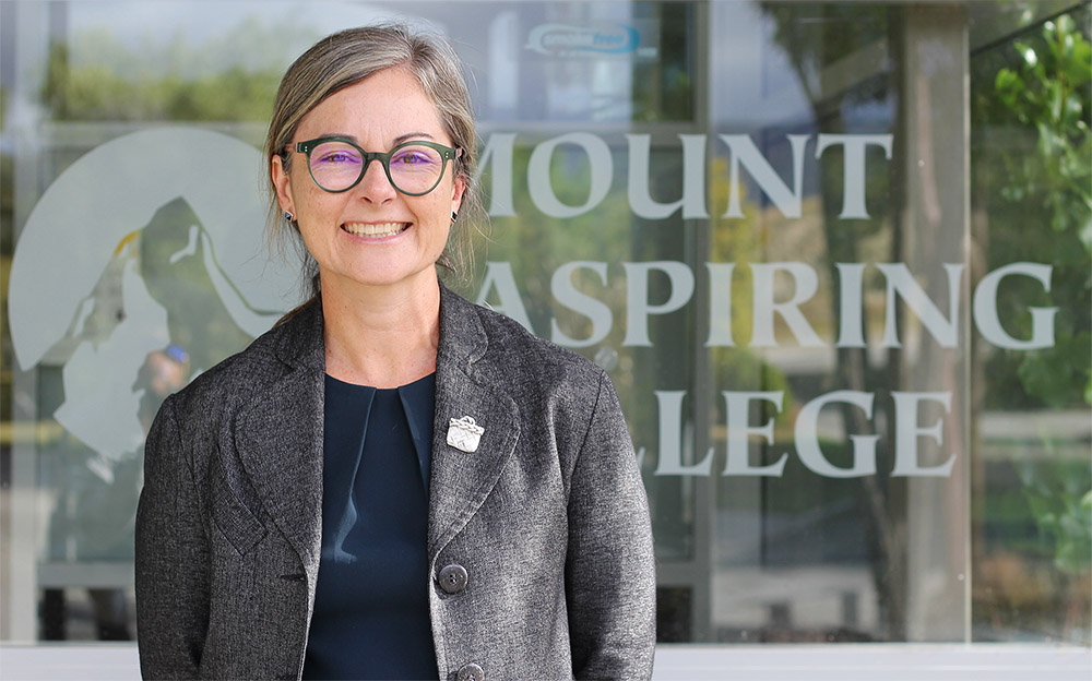 Nicola Jacobsen, Mount Aspiring College's Principal, in front of the college's entrance